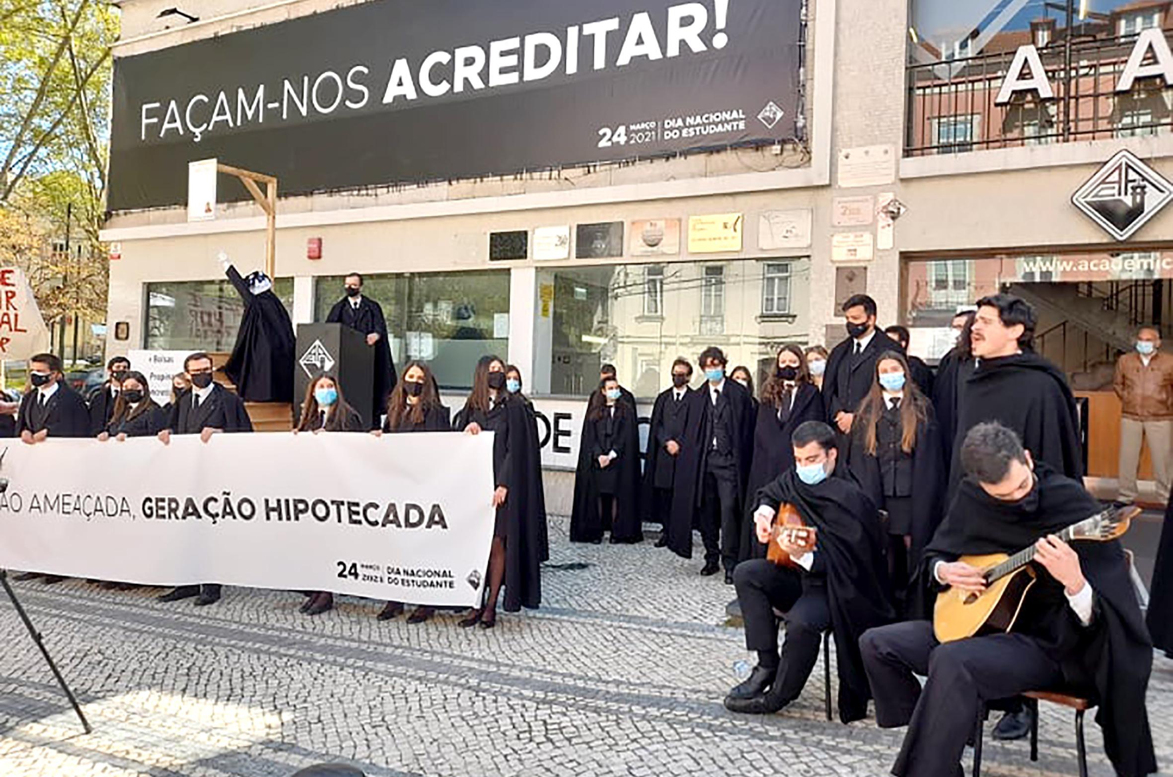 """Grupo de estudantes trajados em frente à Associação Académica de Coimbra. Vêm-se cartazes """"Façam-nos Acreditar"""" e """"Geração Ameaçada, Geração Hipotecada""""; dois estudantes tocam guitarra e os restantes, cerca de 20, prestam atenção com postura de protesto contra o sistema"""